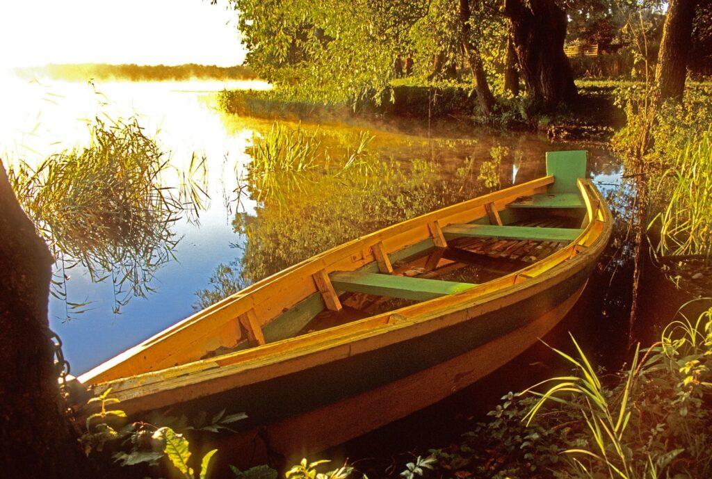 Zdjęcie łódki na jeziorze przy brzegu o wschodzie słońca