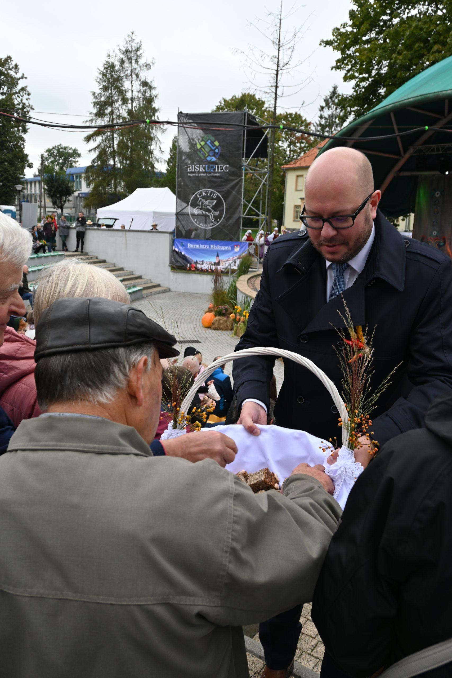 Burmistrz Biskupca rozdaje dożynkowy chleb